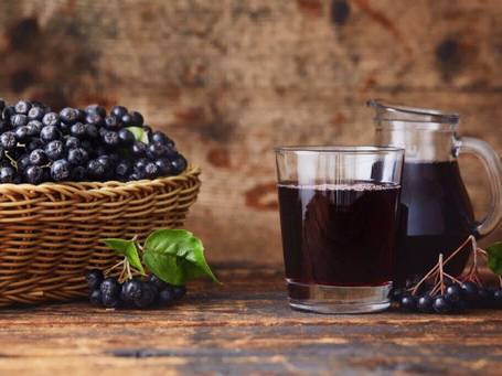 Aronia juice in glass next to Aronia berries