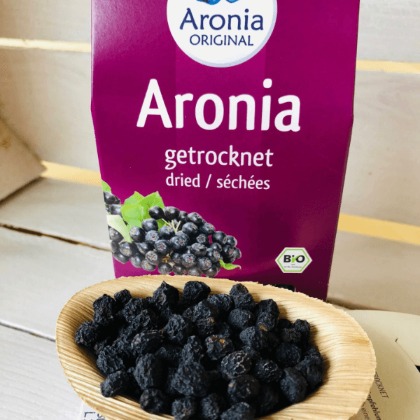 organic dried aronia berries on wooden spoon